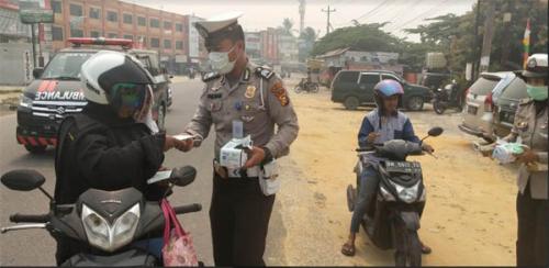 Peduli Bahaya Asap, Satlantas Polres Siak Bagikan Masker kepada Warga