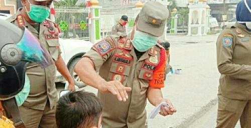Peduli Kabut Asap, Satpol PP Pelalawan Bagikan Masker pada Pengendara di Jalan Raya